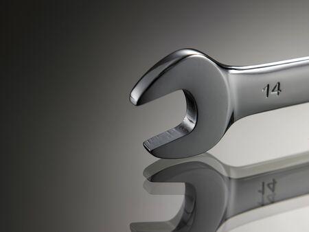 Nahaufnahme des Schraubenschlüssels auf grauem Hintergrund mit Reflexion