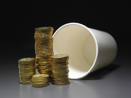 stack of gold coin in front of paper cup