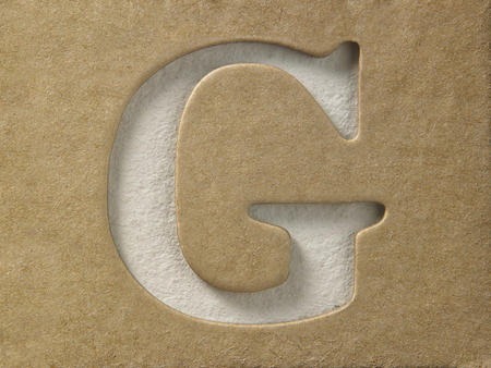 recorta el alfabeto g en la cartulina marrón Foto de archivo