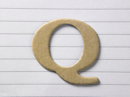 close up of alphabet q on single line book