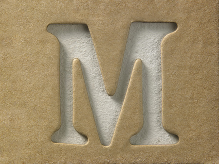 cut out alphabet m on the brown cardboard Stock Photo