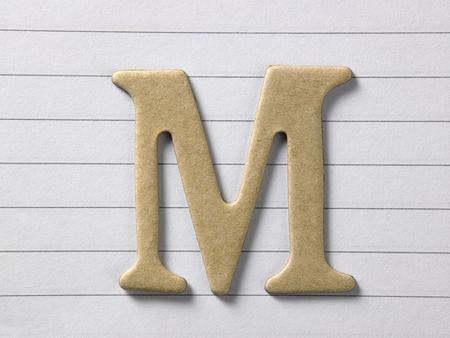 primo piano dell'alfabeto m su un libro a riga singola
