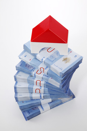 modal house on top of money stacked high Stock Photo