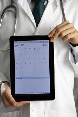 Doctor holding and showing digital tablet. Stock Photo