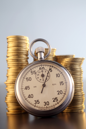 stop watch with stack of coin Imagens