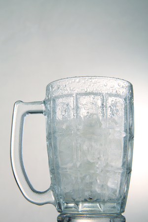 photo of empty glass with ice cubes on white background