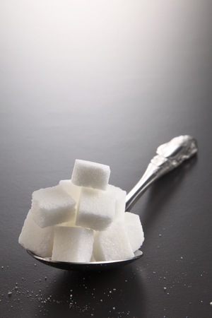 big or super size spoon with pile of cube white sugar Standard-Bild