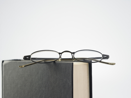 pair of reading glasses rest on top of book