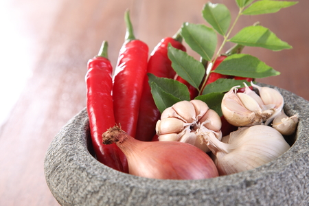 garlic,onion,curry leaf and chilli with mortar for spicy thai ingredient Stock Photo