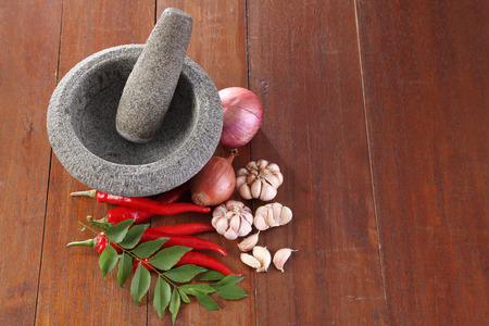 mortar and spices on top of the wooden table