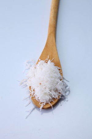 shredded coconut on the wooden spoon Imagens