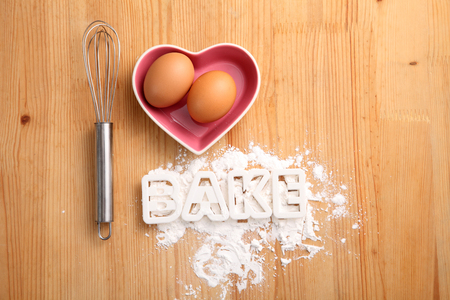 baking concept,hand whisk and eggs in a heart shape container Reklamní fotografie - 118050897