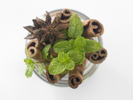 Sticks of cinnamon with mint and anise on a white background