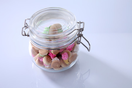 Belly button iced gem biscuits in a glass jar Archivio Fotografico