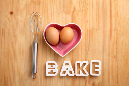 baking concept hand whisk next to eggs in a heart shape container Reklamní fotografie