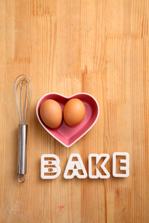 baking concept hand whisk next to eggs in a heart shape container Reklamní fotografie - 118056845