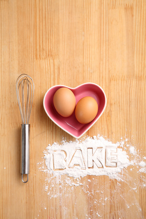 baking concept,hand whisk and eggs in a heart shape container