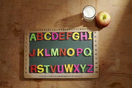 apple and glass of milk by a blackboard with colorful alphabet