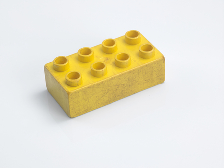 old yellow Plastic building blocks on white background