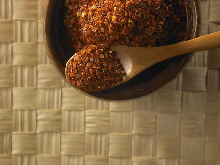 coarse chili powder on the wooden bowl Imagens
