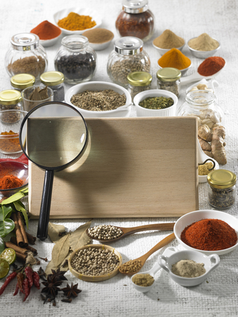 Blank wooden board with a magnifier and spices in the background.