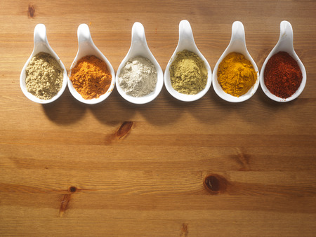 assorted curry powder in saucers on the wooden background
