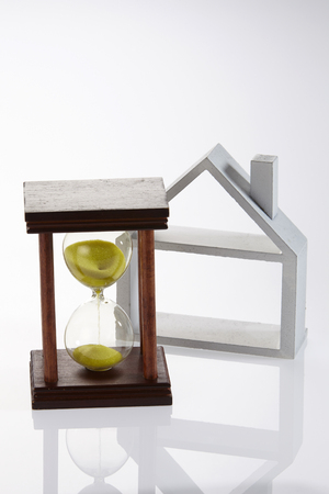 model house and hour glass on the white background Stock Photo