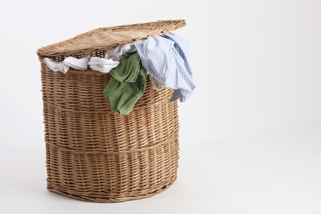 rattan laundry basket full of clothes and towels for washing Standard-Bild