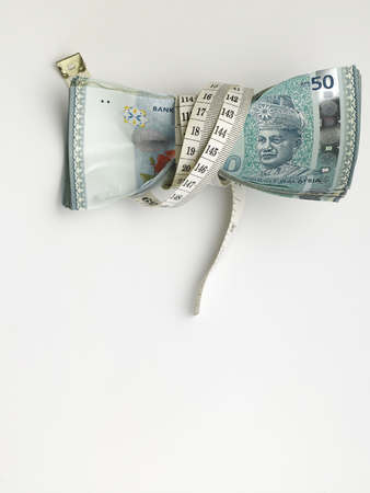 stack of malaysia ringgit tight with measuring tape