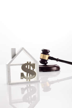 gaval hammer with model house with dollar sign on the white background 写真素材
