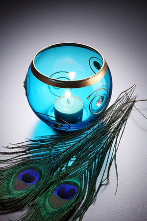 blue round tealight wit peacock feather