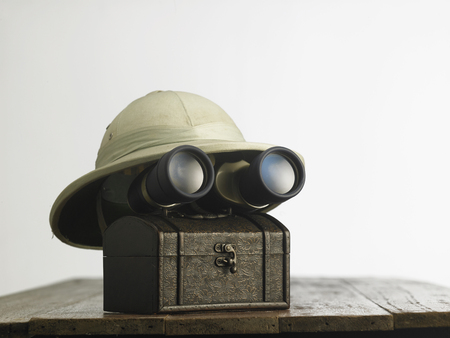 Old colonial hat with a pair of  binoculars on wooden table