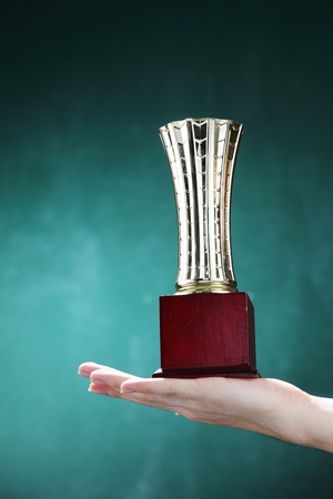 hand holding up a gold trophy cup on the blackboard Imagens