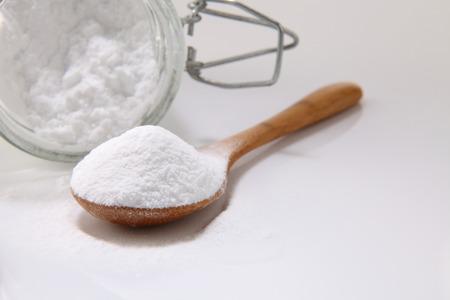 Cuchara de madera llena de bicarbonato de sodio sobre el fondo blanco. Foto de archivo