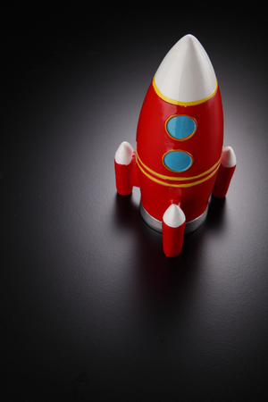 rocket shape coin box on the gray background