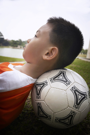 Boy lying on soccer ball