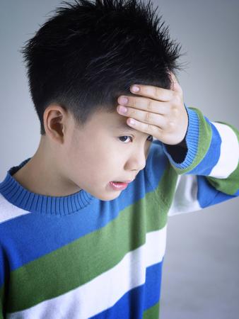 Boy touching his forehead Banco de Imagens