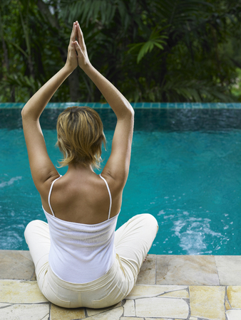 back view of a girl meditating by the pool side Imagens