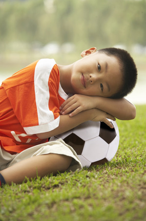 Boy lying on soccer ball