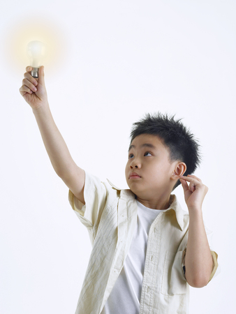 Boy holding a light bulb while snapping his fingers