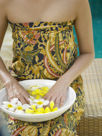 Woman soaking her hands in a bowl of flower water
