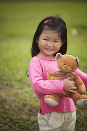 Girl hugging teddy bear Stockfoto