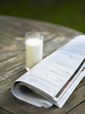 a glass of milk and newspaper on the table