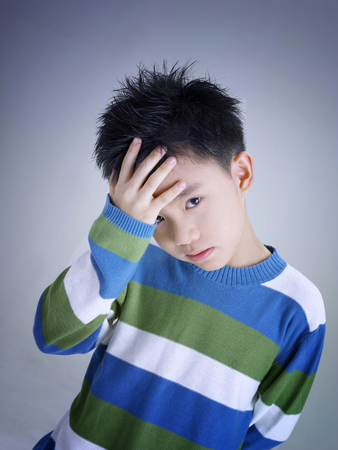 Boy touching forehead Stockfoto