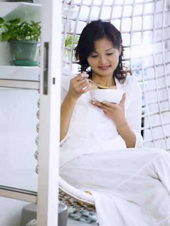 woman eating cereal in the garden Banco de Imagens