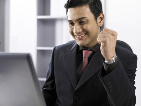 Businessman looking at laptop, hands in fists, smiling