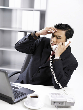 businessman with hand on his forehead while answering the phone