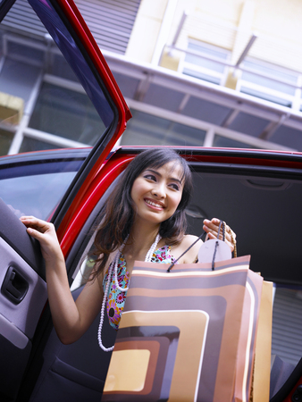 woman with shopping bags, out from the car Stock Photo