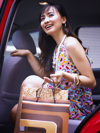 woman getting out from the car with shopping bags