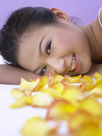 woman lying down with rose petals around her Stock Photo